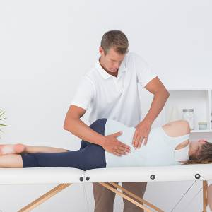 Osteopath treating at table